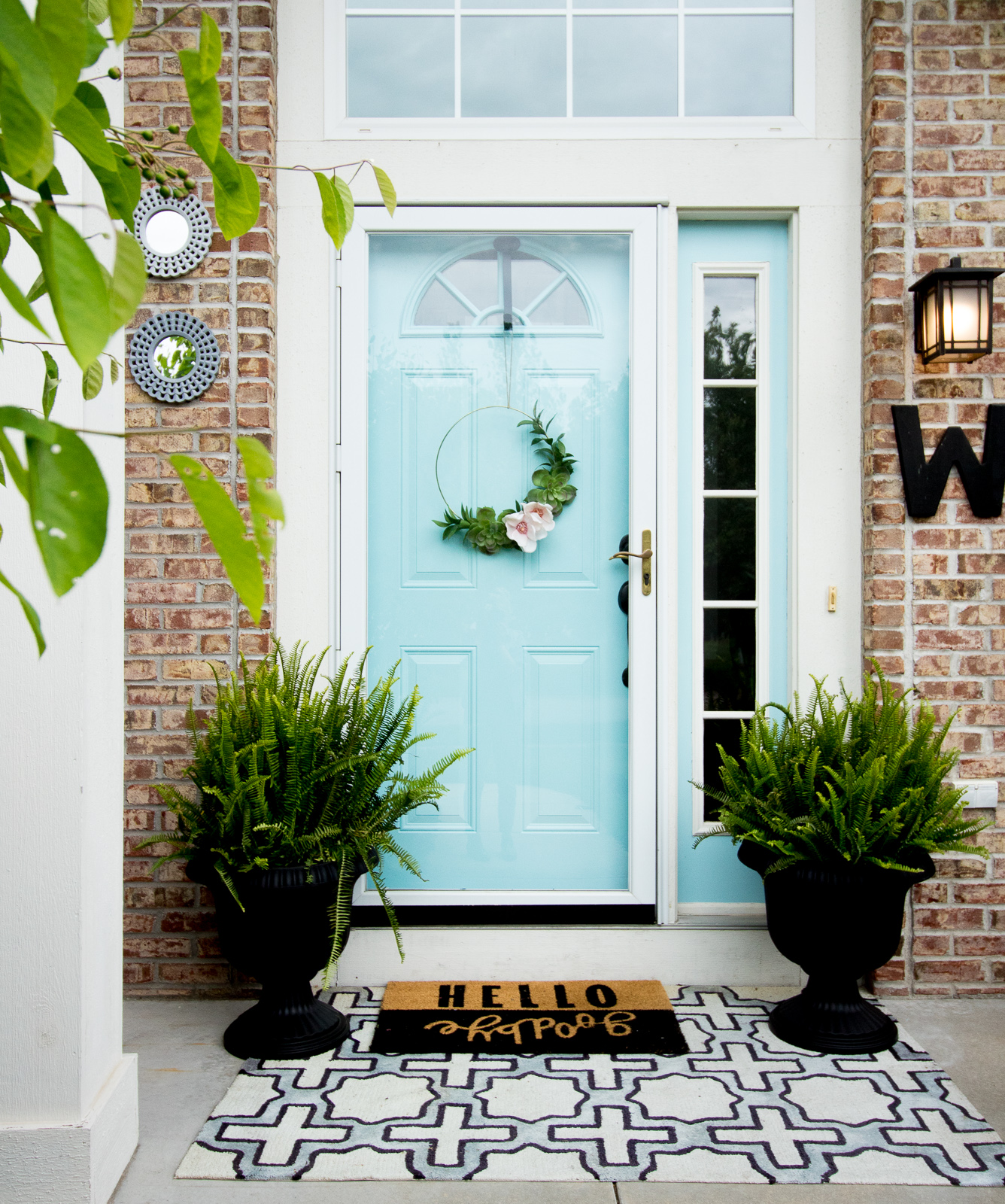budget friendly ways to spruce up your front porch like painting your door, buying an outdoor rug, and a DIY gold hoop wreath